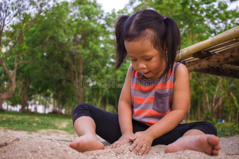 Happy child playing with sand, Funny Asian family in a park stock photos