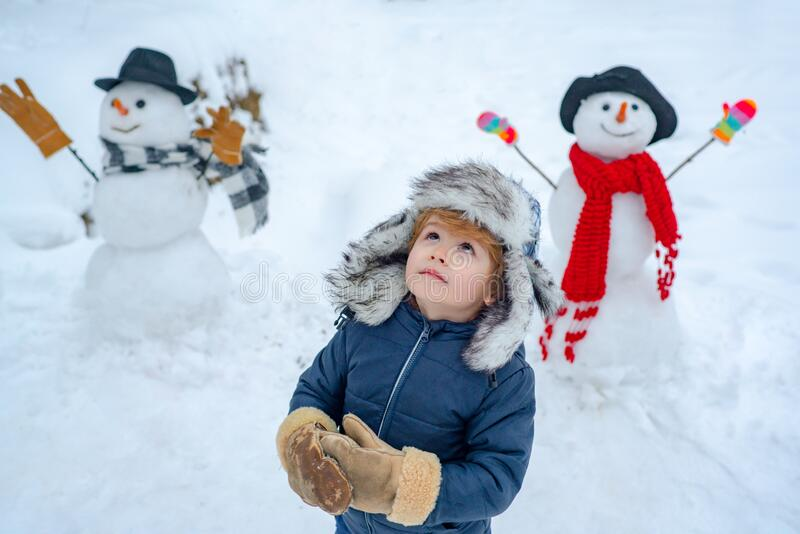 Happy child playing with snowball against white winter background. Winter portrait of cute child in snow Garden. stock photo