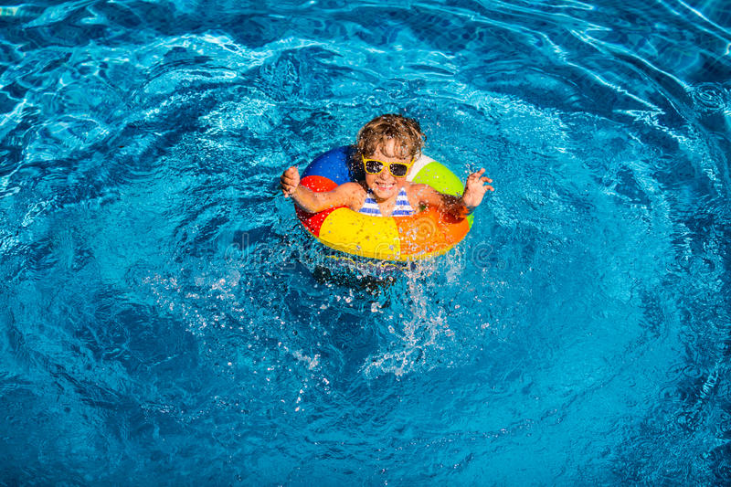 Happy child playing in swimming pool. Summer vacation concept. Top view portrait stock photography
