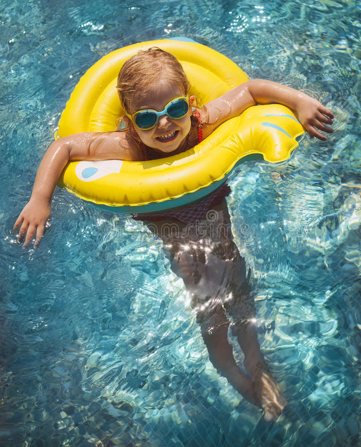 Happy child playing in swimming pool. Summer vacations concept royalty free stock photography