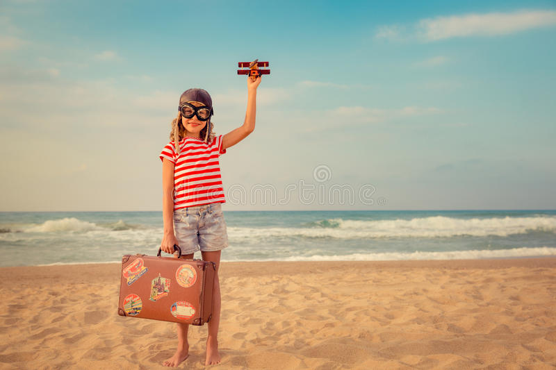 Happy child playing with toy airplane. Against sea and sky background. Kid pilot having fun outdoor. Summer vacation and travel concept. Freedom and imagination royalty free stock photography