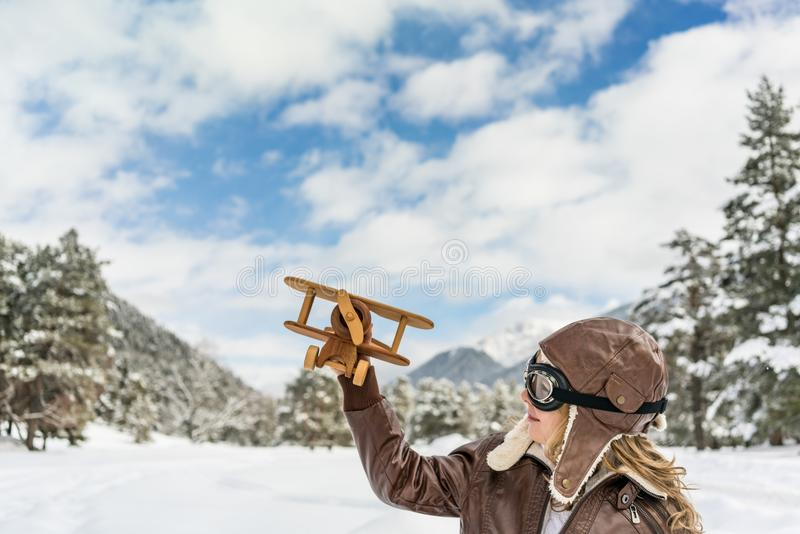 Happy child playing with toy airplane. Against winter sky background. Kid pilot having fun outdoor. Imagination and freedom concept royalty free stock image