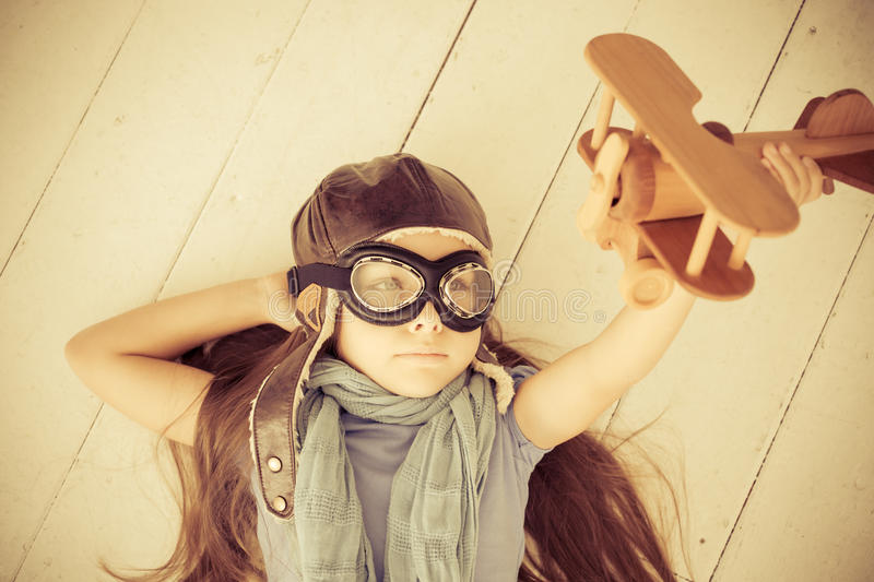 Happy child playing with toy airplane. Kid lying on wooden floor at home. Retro toned royalty free stock photography