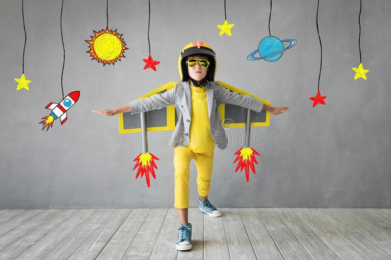 Happy child playing with toy jet pack royalty free stock photos
