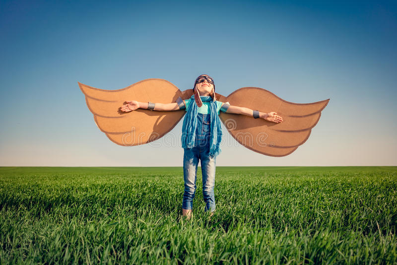 Happy child playing with toy paper wings stock images