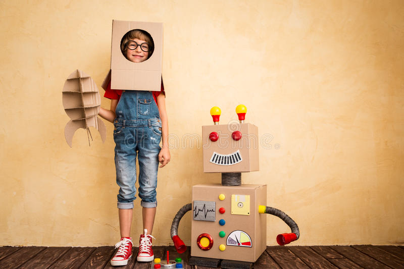 Happy child playing with toy robot. At home. Innovation technology and success concept royalty free stock photo