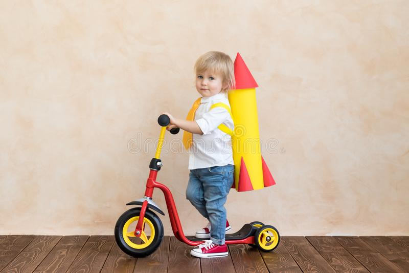 Happy child playing with toy rocket at home stock photos