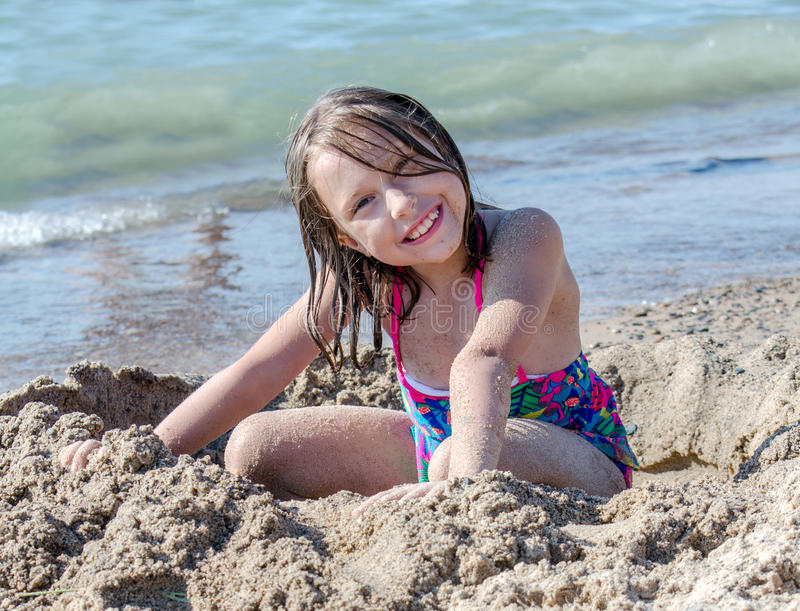 Happy child plays in a hole in the sand stock photos