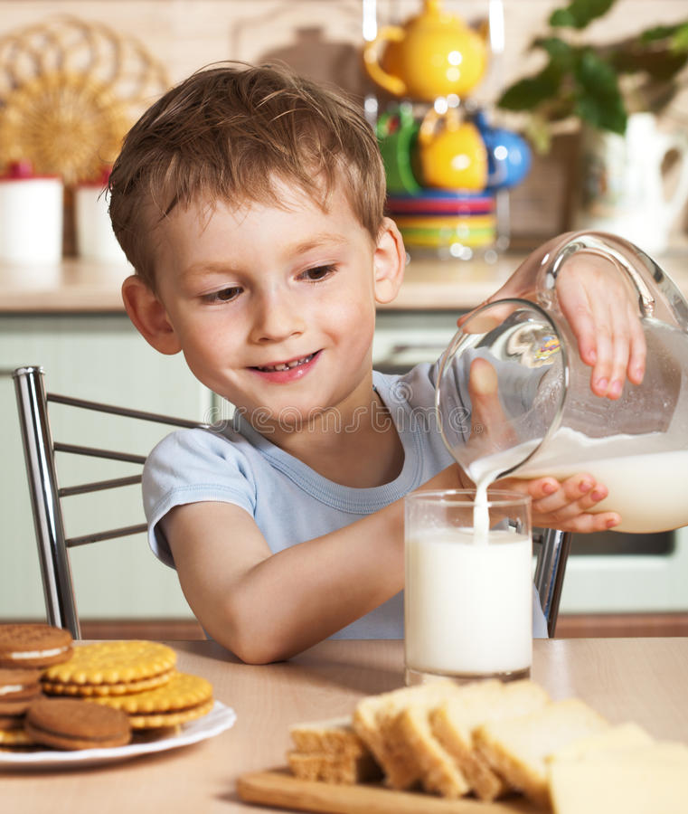 Download Happy Child Pours Milk From Jug Stock Image - Image: 9412083