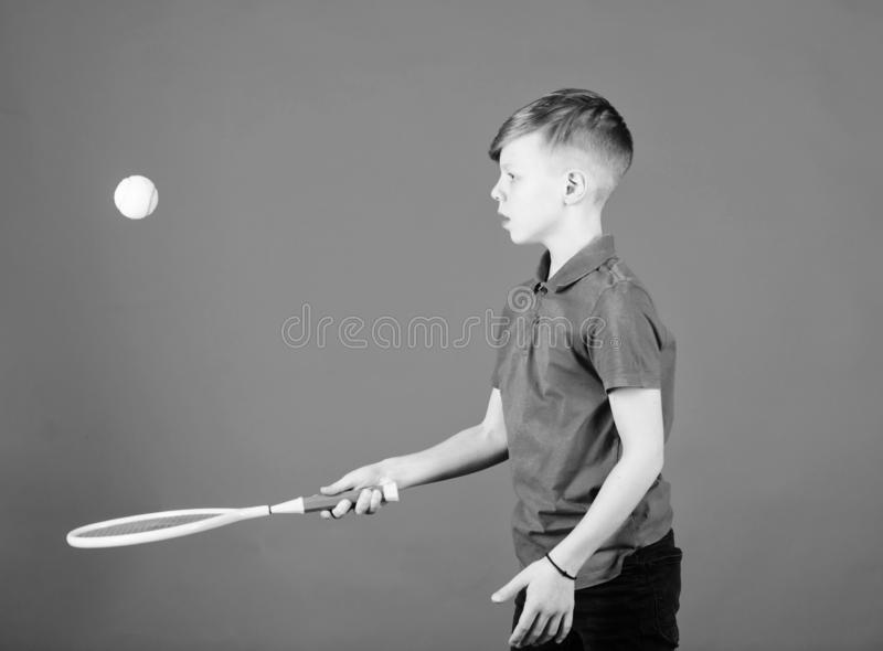 Happy child practice tennis. Little boy practice. Fitness diet brings health and energy. Gym practice of teen boy. Tennis player with racket and ball stock photos