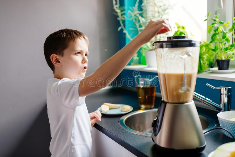 Happy child preparing fruit cocktail in kitchen royalty free stock image