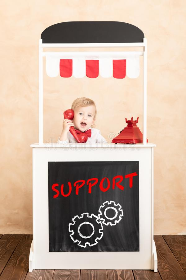 Education, start up and business idea concept. Happy child pretend to be businessmen. Funny kid speaking by phone. Education, start up and business idea concept royalty free stock photo