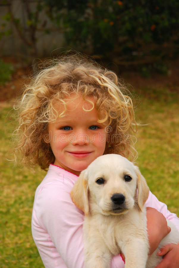 Happy child with puppy pet. Outdoor portrait of a beautiful little caucasian girl child smiling, sitting and holding her cute Labrador Retriever dog puppy in the royalty free stock photography