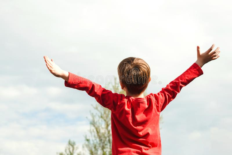 Happy child raising hands up at nature. Health, freedom and future concept. Happy childhood. Fresh air, environment. Dream of. Flying. Little boy enjoying sunny royalty free stock photos