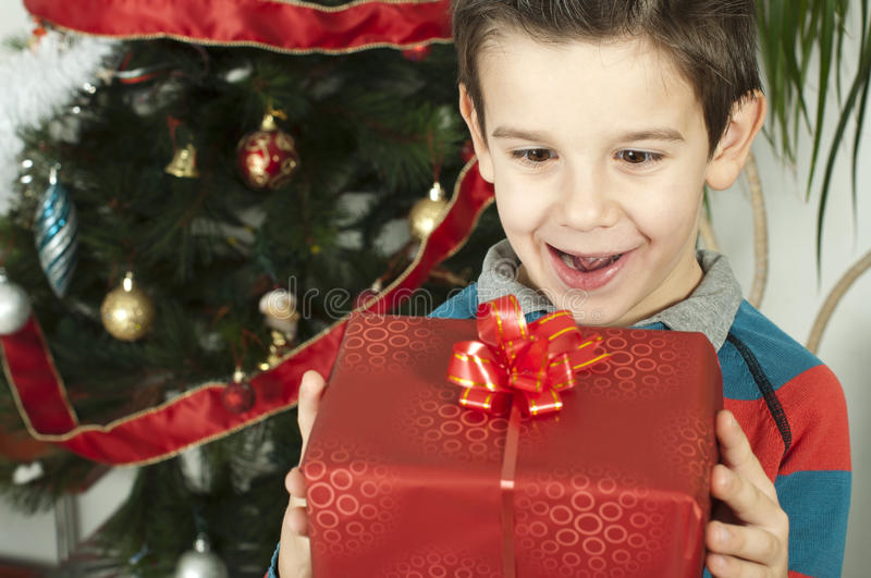 Happy child receive the gift of Christmas. In front of the Christmas tree royalty free stock images