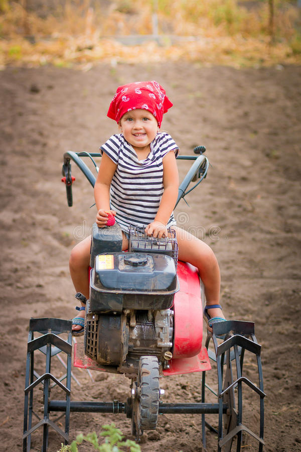 Happy child in red bandana and stripe tee sits on tiller on the field. baby girl driver cultivator stock photos