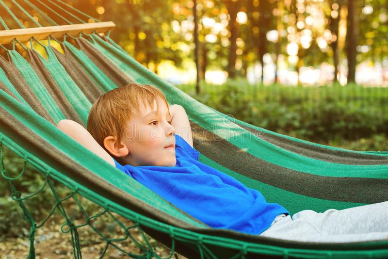 Happy child relaxing in hammock. Summer vacation concept. Cute boy lying in a hammock in garden, dreaming. Happy and healthy royalty free stock photo