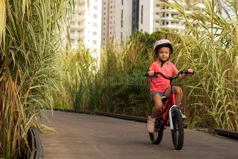 Happy child rides a bike on bike path. Cyclist child girl enjoys good weather and cycling royalty free stock photography