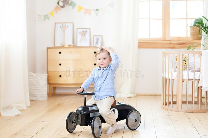 Happy child riding toy vintage car. Funny kid playing at home. Summer vacation and travel concept. Active little boy driving a car stock photos
