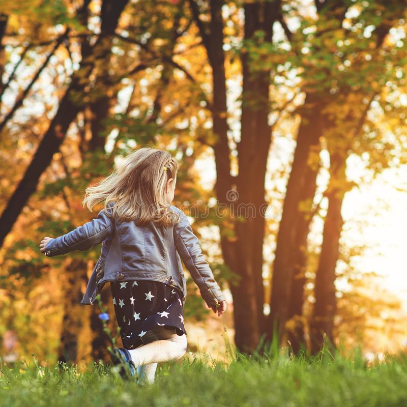 Happy child running at autumn park. Little girl playing outdoors. Beautiful golden autumn time. Happy and healthy childhood. Autum. N kids fashion. Autumn royalty free stock photos
