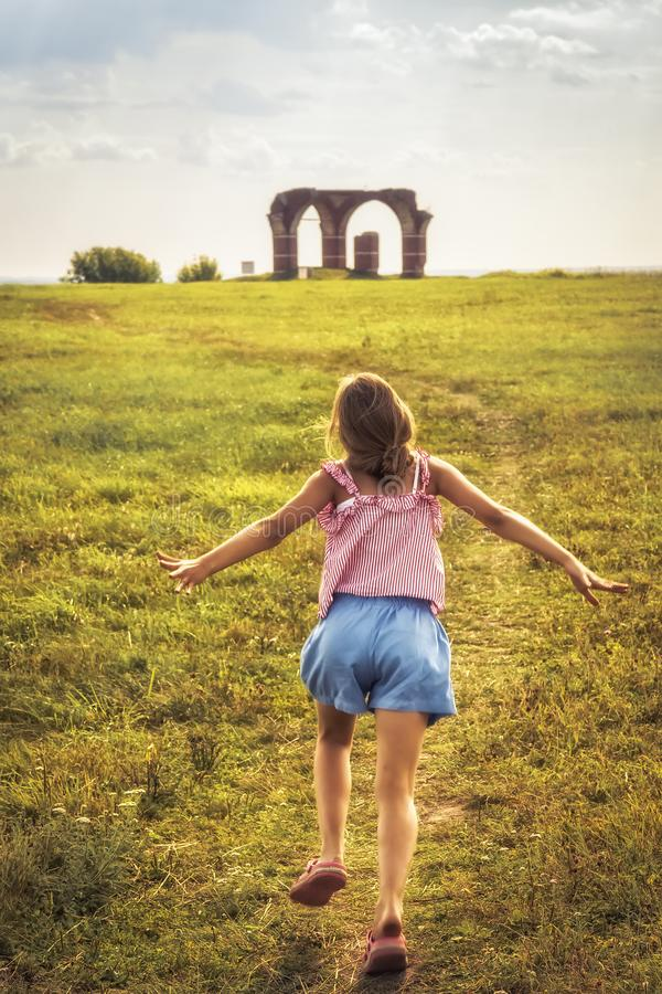 Happy child running on summer field with outstretched arms towards horizon concept happy carefree childhood lifestyle. Happy child running on summer field with stock photos