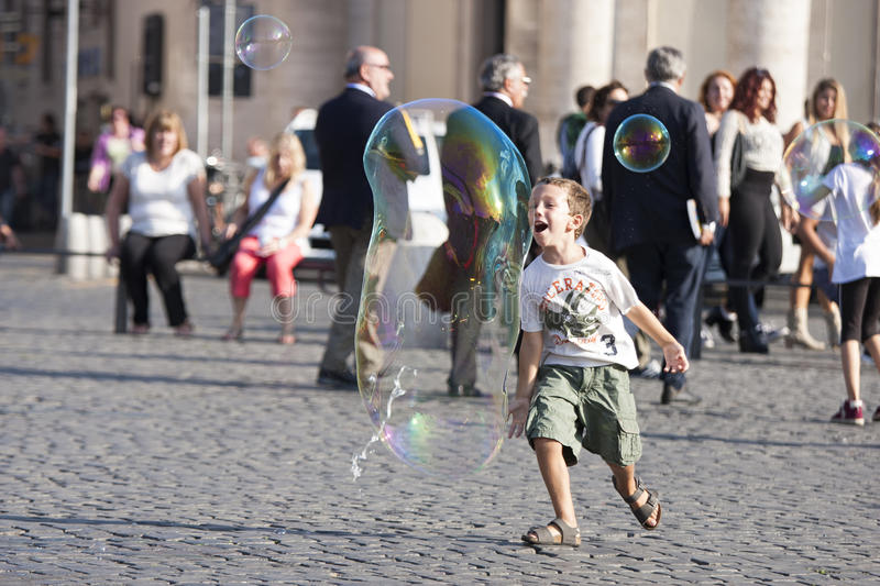 Happy child running towards a soap bubble. A happy child is running to reach a large soap bubble. Behind him there are many tourists in Piazza del Popolo in Rome stock images