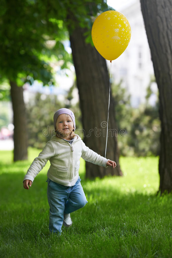 Happy child running with a yellow balloon royalty free stock photos