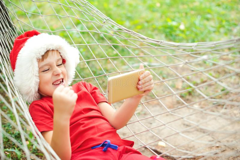 Happy child in Santa hat screaming yes! Excited boy lying in hammock and playing online games. Happy Christmas holidays. Christmas stock photography