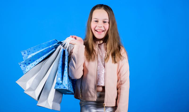 Happy child in shop with bags. Shopping day happiness. Buy clothes. Fashionista addicted buyer. Fashion boutique kids royalty free stock photography