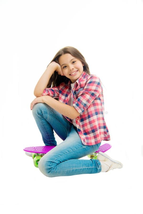 Happy child sit on penny board isolated on white. Little girl smile with beauty look. Carefree kid with skateboard stock photo