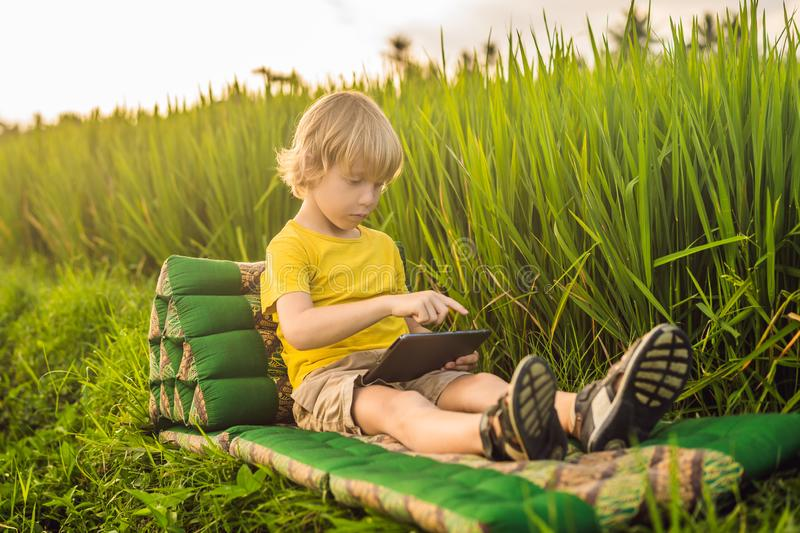 Happy child sitting on the field holding tablet. Boy sitting on the grass on sunny day. Home schooling or playing a. Tablet stock images