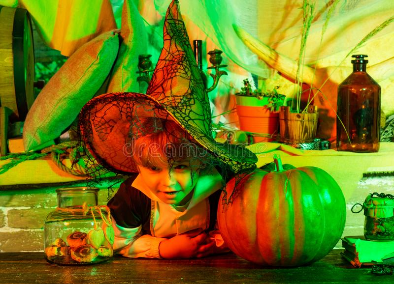 Happy child with skeleton costume holding and eating candies. Halloween interior. Funny kid in carnival costumes indoors. Home Halloween atmosphere royalty free stock photos