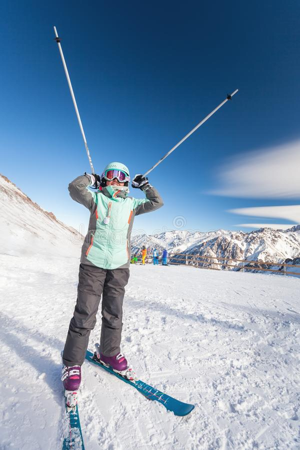 Happy child skier in mountains holds up ski poles. Ski lesson alpine school. royalty free stock image
