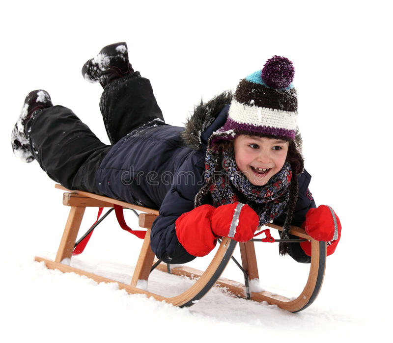 Happy child on sledge in winter, winter sports stock photography