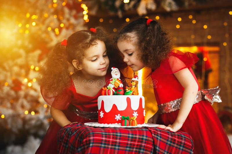Happy child smile and laugh near Christmas cake. Twin curly hair sisters stock photography