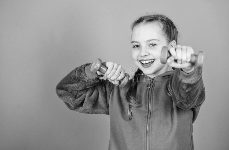 Happy child sportsman with barbell. Fitness diet for energy health. workout of small girl sportsman hold dumbbell. Weight lifting for muscules. Childhood royalty free stock image