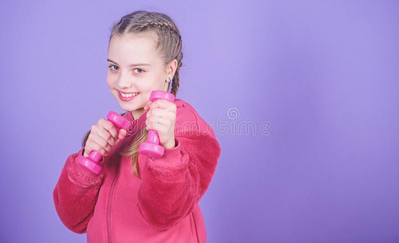 Happy child sportsman with barbell. workout of small girl hold dumbbell. weight lifting for muscules. Childhood activity. Fitness diet for energy health. Sport stock photography