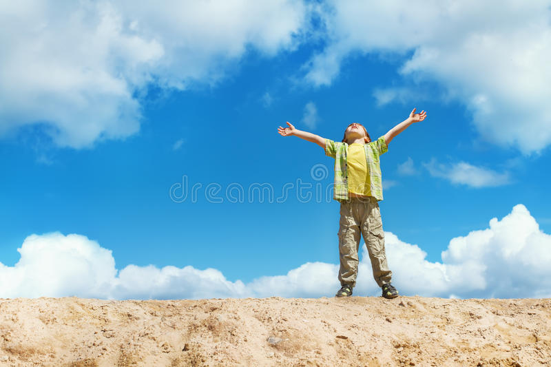 Download Happy Child Standing With Hands Raised Up Over Sky Stock Photo - Image of caucasian, landscape: 25562580