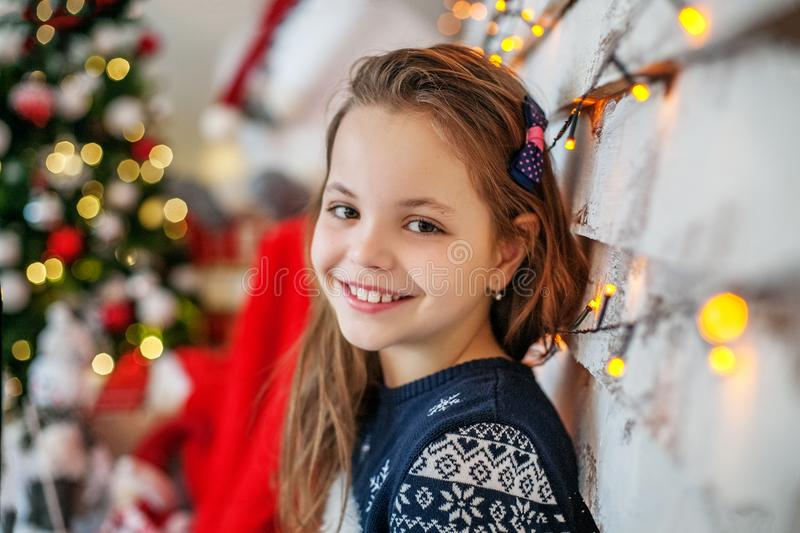 Happy Child student sitting near the Christmas tree. The concept stock photo