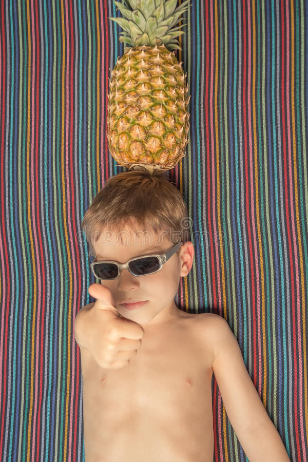 Happy child with sunglasses and pineapple in head stock photos