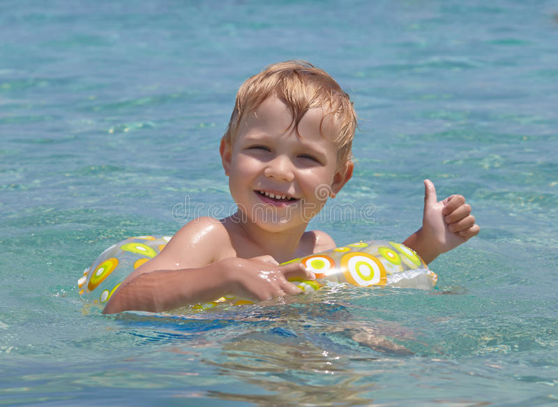 Happy child swimming in the sea. Summer vacation concept royalty free stock image