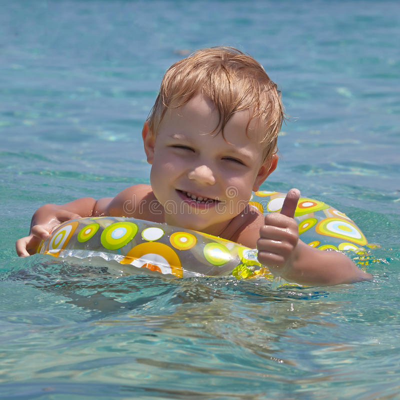 Happy child swimming in the sea. Summer vacation concept royalty free stock photos
