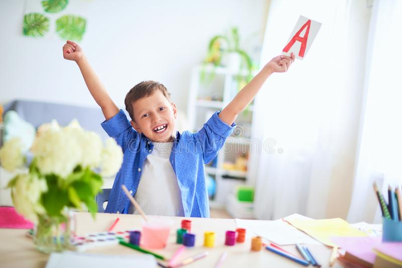 Happy child at the table with school supplies smiles funny and learns the alphabet in a playful way.positive student in a bright royalty free stock photography