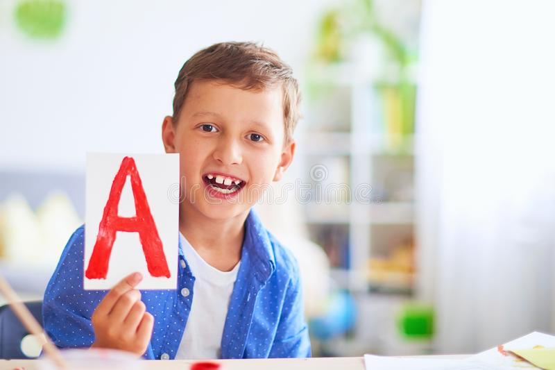 Happy child at the table with school supplies smiles funny and learns the alphabet in a playful way.positive student in a bright. Boy does his homework at home royalty free stock images