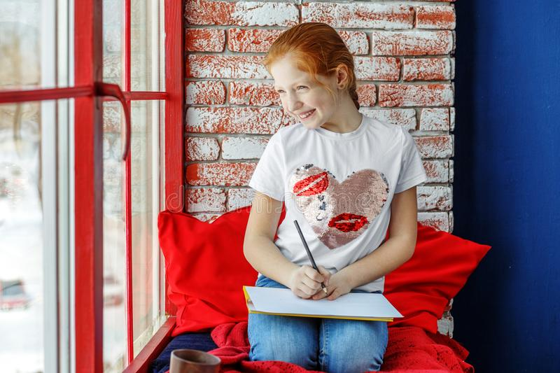 Happy child is a teenager sitting on a window sill and drawing. royalty free stock photography