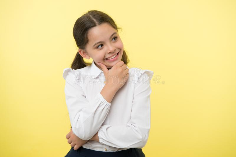 Happy child thinking on yellow background. Little daydreamer girl with cute smile. Lost in thoughts. Your dreams can royalty free stock photos