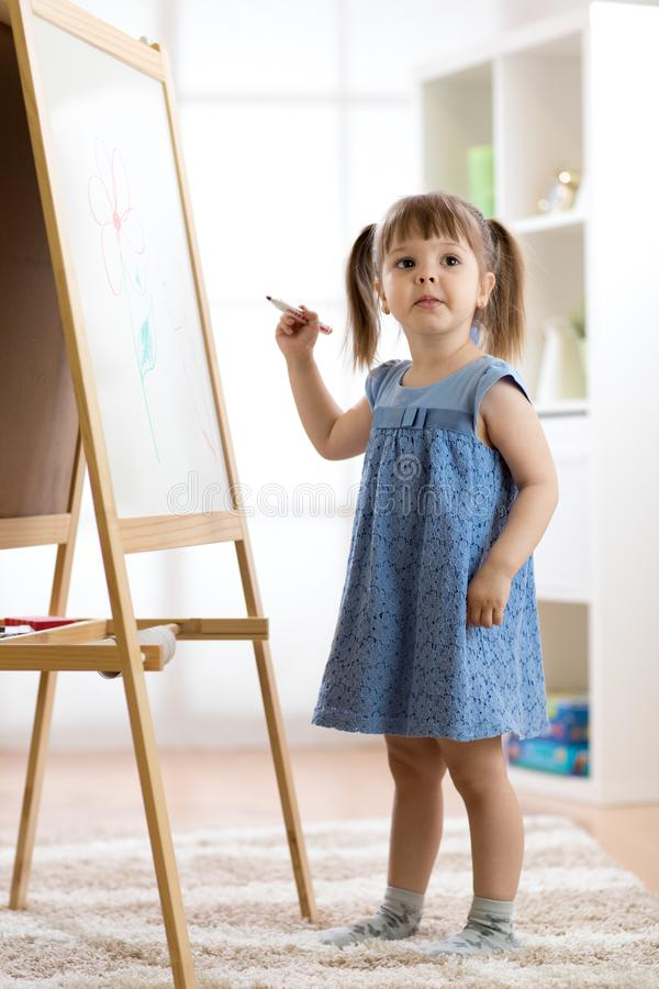 Happy cute toddler girl drawing or writting with marker pen on a blank whiteboard at home, preschool, daycare or. Happy child toddler girl drawing or writting royalty free stock photo