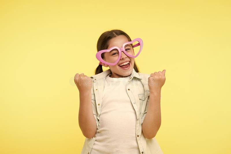 Happy child wear heart shaped glasses on yellow background. Little girl smile in fashion accessory. Funky style beauty stock photography