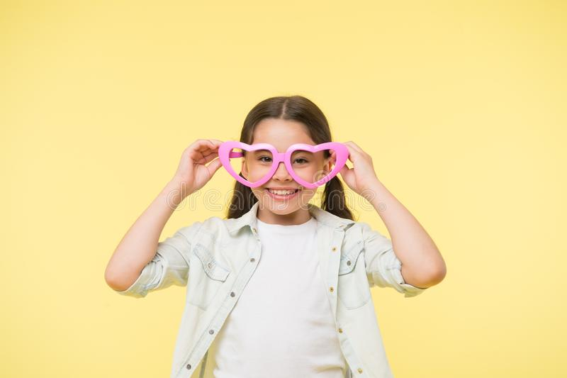 Happy child wear heart shaped glasses on yellow background. Little girl smile in fashion accessory. Summer fashion look. Funky style beauty. Young and royalty free stock photography
