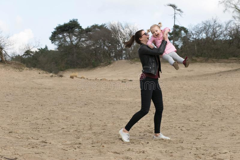Child and woman playing in the sand stock photos